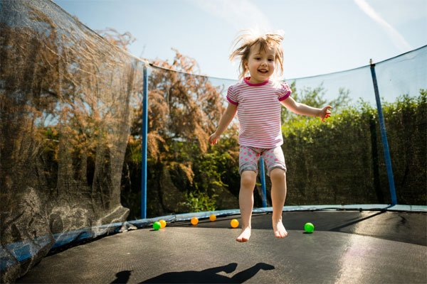 photo of toddler jumping on trampoline